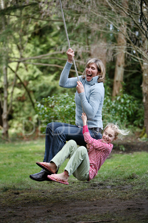 Former Olympian Silken Laumann plays with her daughter Kate, age eight, on a rope swing in their backyard in Victoria, British Columbia. Photo assignment for the Globe and Mail national newspaper in Canada.