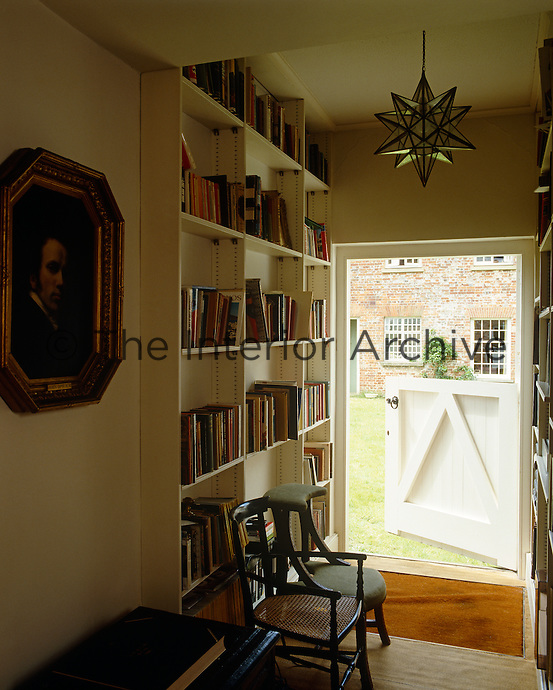 A corridor leading to an open stable door is lined with bookshelves