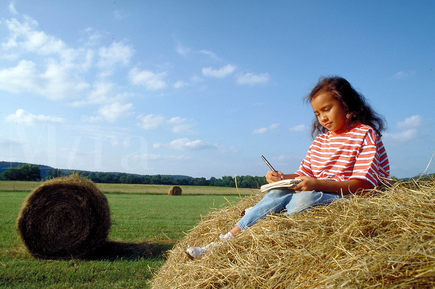 10 year-old Cherokee girl writing in her journal on a hayroll in a field.  Tahlequah, OK