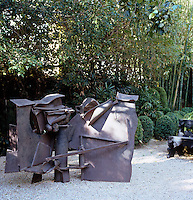 A metal sculpture in the garden strikes a contemporary note against the backdrop of box and bamboo