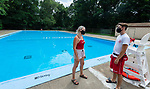 WATERBURY , CT-073020JS18—On a slow day at the Fulton Park Pool in Waterbury on Thursday, first year lifeguards Marley Thompson of Watertown and Noah Scott of Prospect,  chat in front of an empty pool. The  new rules and limits on use of city pools in an effort to prevent the spread fo COVID continues. <br /> Jim Shannon Republican-American