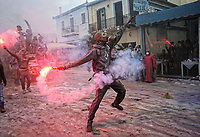Pictured: A flour wars participant with a flare in Galaxidi, Greece. Monday 19 February 2018<br /> Re: Clean Monday (Monday of Lent) celebration of flour wars (Alevromoutzouroma) in the town of Galaxidi, which coincides with the beginning of the Greek Orthodox Lent in Greece. The origins of the custom are unclear, however it appears in its current form since the mid-19th century.<br /> Locals and visitors of all ages gather to collect large quantities of flour which they throw to each other. Various types of coloring is added for effect while people paint their faces with charcoal.
