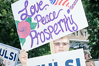 A supporter of Democratic presidential candidate and Hawaii representative Tulsi Gabbard holds signs before the 4th of July parade in Amherst, New Hampshire, on Thu., July 4, 2019.