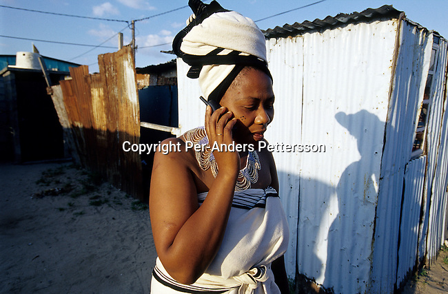 Beaulas Gcwabe, a hair saloon owner talks on her mobile phone outside a shack on August 23, 2001 in Site C Khayelitsha, a township about 35 kilometers outside Cape Town, South Africa. She's dressed in a traditional Xhosa dress and is attending a bridal shower in the township. Khayelitsha is one of the poorest and fastest growing townships in South Africa. (Photo by: Per-Anders Pettersson).