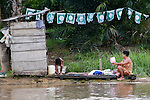 A family bathes and washes clothes on the banks of the Kinabatangan River on Monday April 29th 2013 in Bilit, Malaysia. (Photo by Brian Garfinkel)