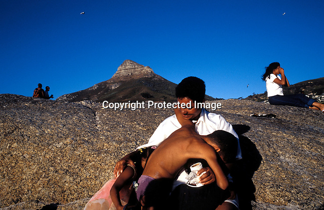 DIPPLEi00027.Holiday makers taking cover during a sandstorm at sunset on January 1, 2003 in Camps Bay, South Africa. Camps Bay has some of the best beaches and most expensive properties in the country. .©Per-Anders Pettersson/iAfrika Photos