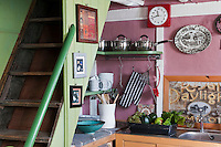 A steep ladder staircase, with a cupboard and marble-topped work surface below it, leads directly from the cosy kitchen to the bedrooms above