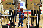 "Molly Best, 4, wears a Spiderman costume as she holds hands with her father , Jera, while voting in Storey Gym Tuesday afternoon. When asked why Molly was wearing the costume her father replied 'To protect the voters."" Michael Smith/staff"
