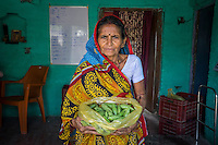 A producer group farmer holds a handful of vegetables at the collection centre in Machahi village, Muzaffarpur, Bihar, India on October 27th, 2016. Non-profit organisation Technoserve works with women vegetable farmers in Muzaffarpur, providing technical support in forward linkage, streamlining their business models and linking them directly to an international market through Electronic Trading Platforms. Photograph by Suzanne Lee for Technoserve