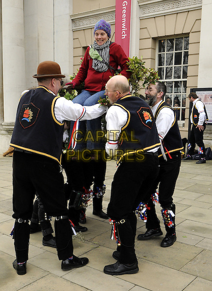 Blackheath Morris Men act out the ritual known as 'Easter Lifting' in Greenwich, London. The tradition involves the lifting of a female volunteer into the air 3 times before being asked to kiss each of those doing the lifting .April 1st 2013.gv general view full length black white shirt bells profile dance dancing  chair sitting lifting carrying .CAP/BK/PP.©Bob Kent/PP/Capital Pictures