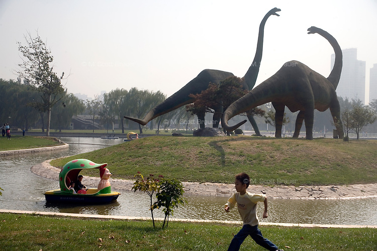 Dinosaur statues stand above a boat ride area in the Tianjin Zoo in Tianjin, China.