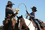 A cowboy on horseback showing his son how to throw a rope to catch cattle roping lasso