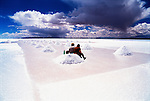 Two miners take a break from work and sit on a pile of salt mined from the salt flats at Uyuni, Bolivia.