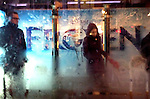 Chicago scenes:  Commuters seek shelter under a bus stop as the winter season's first ice storm pummels downtown Chicago during the evening rush hour. (Photo by Jamie Moncrief)