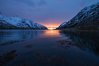 Midday sun hangs low over the horizon in early January, Skjelfjord, Flakstadøy, Lofoten Islands, Norway