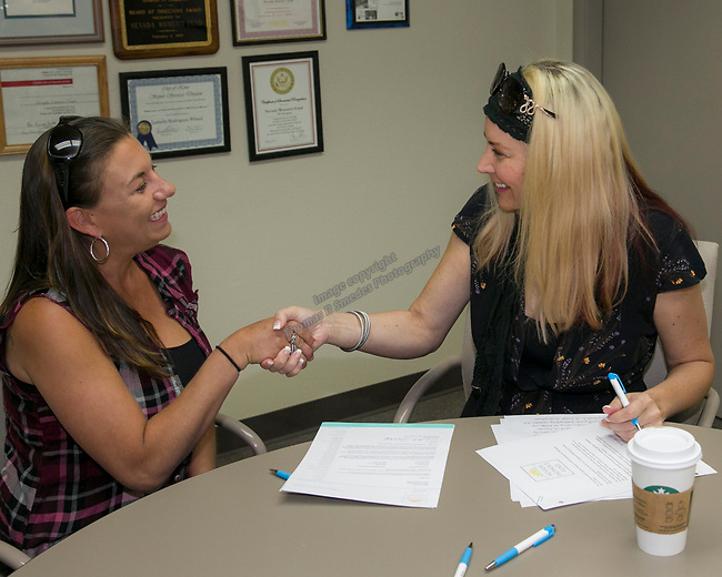 Briann Fletcher, left, gets the details of her scholarship from Board Member Christina Stoever-Young during the Nevada Women's Fund Scholarship distribution, June 20, 2019.