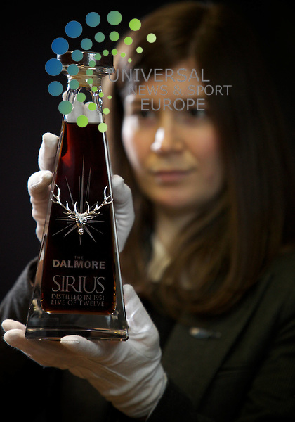 """Natasha Raskin, Gallery Manager, McTears Auctioneers, Glasgow holds a bottle of Dalmore Sirius, a rare single malt Highland Whisky estimated to fetch £25000 when it goes to auction, along with 11 other such bottles, at McTears on 18 January 2012. Dalmore's Master Distiller Richard Paterson, states """"Distinguished and elegant, age has gracefully finessed this brilliant expression. Sirius is, quite simply, one of the world's most perfect whiskies.""""  Picture by Guy Hinks/Universal News and Sport (Europe)"""
