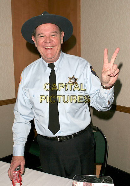 RICK HURST.Hollywood Collectors Show Day One held at Burbank Hilton Hotel Hotel, Burbank, California,18th February 2005..half length sherrif star badge peace sign gesture.Ref: ADM.www.capitalpictures.com.sales@capitalpictures.com.©Capital Pictures.