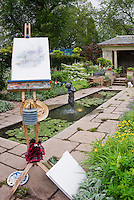 Easel with watercolor drawing in garden setting outdoors with small pond and fountain, summer house, wooden wheelbarrow, painting supplies, stone walkway path, flowers, flowering shrubs, trees, herbs, waterlilies