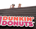 Photo by Phil Grout..GOOD SPORTS, GOOD CAUSE--In keeping with the time-honored.tradition of the alleged fondness police officers have for donuts, Westminster Police Chief Jeff Spaulder (left) and Westminster State Police Commander Andy Winner enjoy their glazed donuts atop the roof.of the local Dunkin Donuts.  Next week they will be living on this roof.until at least $5000 is collected for the Maryland Special Olympics..There will also be other amuzements and displays for the public.