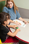Education preschool 3-4 year olds female teacher administering development assesment psychological test to preschool student girl answering questions about block