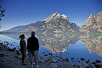 A couple enjoy the grandeur of a Grand Teton reflection upon the still waters of  Jenny Lake in Grand Teton National Park.