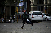 A police commando runs for cover as gunfire rains down from the Taj Mahal Palace Hotel, after multiple terrorist attacks were launched in Mumbai on 26/11/2008..