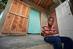 Fourteen-year old Edensly Petithomme does his school homework on the porch of his family's new home in Lareserve, a village near Jean-Rabel in northwestern Haiti. The family's previous house was destroyed during Hurricane Matthew in 2016, and Church World Service, a member of the ACT Alliance, helped the family build their sturdy new home.