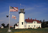 Chatham Lighthouse and keeper's home; daisies in lawn; American and Coast Guard flags in brisk wind. New England coastal town. Chatham Massachusetts.