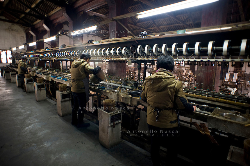 Alcune operaie durante una fase di lavorazione della seta in una vecchia fabbrica.<br /> Wuzhen &egrave; una piccola citt&agrave; della provincia dello Zhejiang chiamata anche la Venezia d'Oriente per la caratteristica dei canali che corrono lungo i vicoli dell'antica citt&agrave;. E' anche riconosciuta come uno dei centri pi&ugrave; importanti per la produzione e la lavorazione della seta nell'antichit&agrave;. Ancora sono presenti alcune piccole ditte che continuano a lavorare la seta con gli stessi metodi di come si faceva da secoli. Nonostante sia diventata una meta turistica ancora si pu&ograve; respirare la vecchia Cina passeggiando tra i vecchi vicoli costruiti con la pietra e rimasti intatti nei secoli.