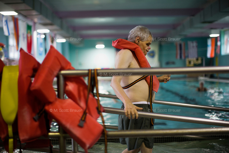 Fernald Developmental Center resident Ronnie Russo waits to get in the pool at the Fernald Center Aquatics pool in the Green Building at Fernald in Waltham, Mass., USA. The twins Ronnie and Randy Russo go to the pool twice a week and, with help from Mike Hebert, walk around the pool with light water weights as a way to get exercise and maintain limb strength.  Hebert was an employee at Fernald, but now volunteers as a swim tutor with the twins twice a week.