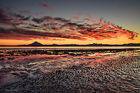 A vivid sunset backlights the clouds and paints the sky orange behind Mount Redoubt and the Aleutian Range.