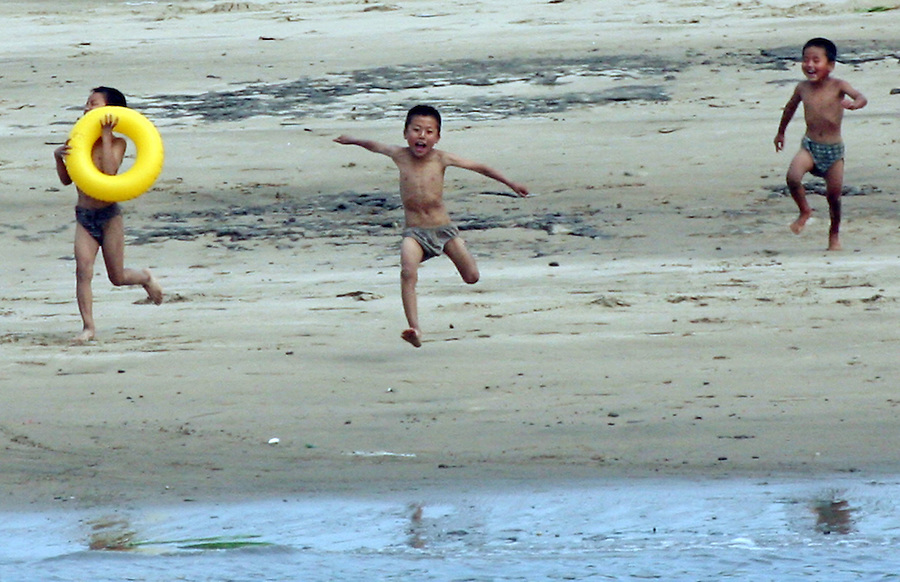 """North Korean gleefully run towards the shore of the Yalu River for a swim in the town of Sinuiju July 8, 2006. China and North Korea are separated by the Yalu River, upon which Chinese tourists take pleaure cruises across the water to  observe their less economically developed neighbors.  North Korea has threatened to take """"stronger physical actions"""" after Japan imposed punitive measures in response to its barrage of missile tests and pushed for international sanctions. North Korea has vowed to carry out more launches and has said it will use force if the international community tries to stop it. DPRK, north korea, china, dandong, border, liaoning, democratic, people's, rebiblic, of, korea, nuclear, test, rice, japan, arms, race, weapons, stalinist, communist, kin jong il"""