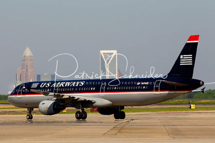 US Airways jet prepares to take off against the Charlotte skyline in the background, at Charlotte-Douglas International Airport in Charlotte, North Carolina. Charlotte-based photographer has other images of transportation, airplanes on runways (and taking off and landing) and interior/exterior airport images of Charlotte-Douglas Intl Airport in portfolio.
