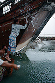 Sur, Oman<br /> July 2001<br /> <br /> Dhow workers clean the hull of a ship and recoat it in the same yard that they build the ships.