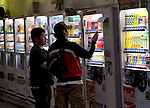 Customers buy drinks from vending machines in Tokyo, Japan on 29 April 2010. Photographer: Robert Gilhooly