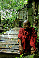 An old Buddhist Mong waiting for the rain to stop, in the temples of Beng Mealea, during the monsoon season, the green color is due to the constant rain during this time of the year