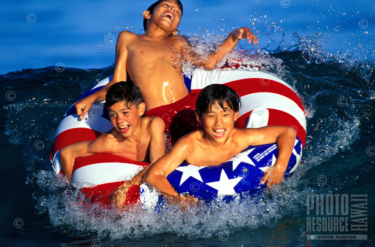 Three boys playing in the ocean in a inner tube