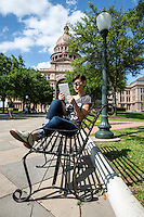 Austin Woman sitting on bench using digital tablet computer at the Texas State Capitol grounds in downtown Austin, Texas.