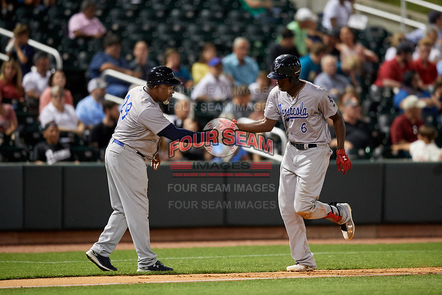 Pensacola Blue Wahoos right fielder Aristides Aquino (6) is congratulated by bench coach Lenny Harris (29) as he rounds third base after hitting a home run in the bottom of the fifth inning during a game against the Birmingham Barons on May 8, 2018 at Regions Field in Birmingham, Alabama.  Birmingham defeated Pensacola 5-2.  (Mike Janes/Four Seam Images)