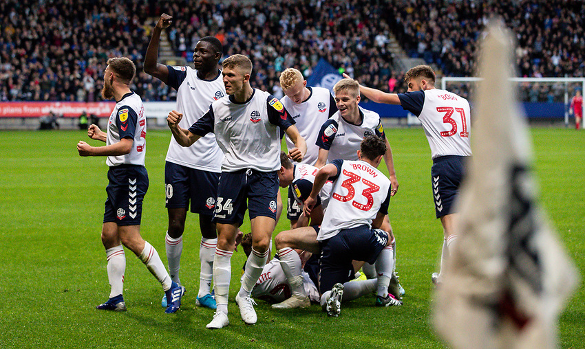Bolton Wanderers' Dennis Politic (lower centre) is mobbed by his celebrating team mates after scoring his sides first goal<br /> <br /> Photographer Andrew Kearns/CameraSport<br /> <br /> EFL Leasing.com Trophy - Northern Section - Group F - Bolton Wanderers v Bradford City -  Tuesday 3rd September 2019 - University of Bolton Stadium - Bolton<br />  <br /> World Copyright © 2018 CameraSport. All rights reserved. 43 Linden Ave. Countesthorpe. Leicester. England. LE8 5PG - Tel: +44 (0) 116 277 4147 - admin@camerasport.com - www.camerasport.com