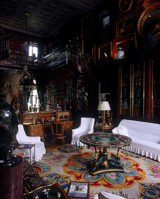 A grand library with a mezzanine level is furnished with tasteful antiques