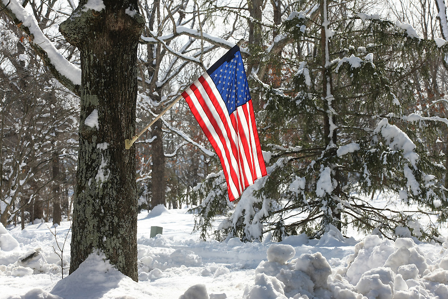 An American flag flying in the snow.