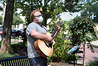 """Brad Bernards Jr. of Cave Springs performs, Sunday, July 26, 2020 for bystandars at the downtown square in Bentonville. """"I have a band and a solo gig, and I'm just working out my kinks,"""" said Bernards Jr. who performs in a band affectionately titled """"The Chil Pollins"""" named after Phil Collins, who he looks up to as a multi-instrument performer. """"It's nice to play out here to get my jitters out. The former Utah resident has started playing shows on the weekends as venues reluctantly open. He's found a regular performance spot at the Aura in Rogers, which opens its parking lot as a performance space he said. Check out nwaonline.com/200727Daily/ for today's photo gallery. <br /> (NWA Democrat-Gazette/Charlie Kaijo)"""