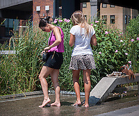 "Visitors to the High Line Park in New York cool off their feet in the ""water feature"" during the heat wave, on Wednesday, July 17, 2013. The heat wave is expected to last for several more days, finally breaking on Saturday.  Meanwhile, the city has issued a heat advisory and has opened up cooling centers in all five boroughs ( © Richard B. Levine)"