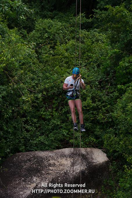 Man with a phone on zipline in Samui beach, Thailand
