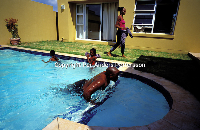 dilsbup00025 People. Buppy Oscar Dube a young successful black guy taking a dip in his swimming pool with some of his daughters friends on March 23, 2002 in Johannesburg, South Africa. He is working for Ericsson, the Swedish mobile phone equipment and phone maker in South Africa. He has reached the life that many blacks want. A nice house in a mainly white gated northern suburb, a beautiful wife, and daughter and a BMW 328I Convertible. Although, he likes his success, he often goes back to Soweto on weekends to wash his car and have a few beers with his friends and relatives. Many blacks that move to the northern suburbs quickly miss the notice and lively life in the township..Photo: Per-Anders Pettersson/iAfrika Photos.