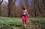 A913H4 Young girl walking in daffodil woods in springtime