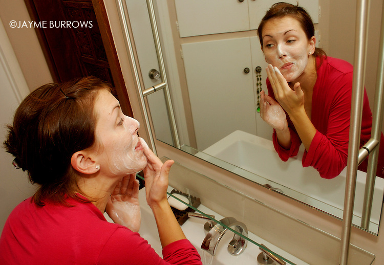 A young woman washes her face and puts on a mask.