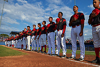 Batavia Muckdogs players and staff stand for the national anthem before a game against the Auburn Doubledays on June 19, 2017 at Dwyer Stadium in Batavia, New York.  L-R:  T.J. Gamba, Brady Fitzgerald, Eric Reigelsberger, Samuel Castro, Thomas Jones, Lazaro Alonso, Rony Cabrera, Terry Bennett, Mathew Brooks, Marcos Rivera, Jhonny Santos, J.C. Millan, Mike Garzillo, Alex Jones, Bryan De La Rosa, Brent Wheatley, Hunter Wells, Shane Sawczak, Manuel Rodriguez, Remey Reed, RJ Peace, Jeremy Ovalle, Travis Neubeck, Ryan McKay, Kenny Koplove, Javier Garcia, Eliezer Cuello, Nestor Bautista, and Horacio Acosta.  Batavia defeated Auburn 8-2 in both teams opening game of the season.  (Mike Janes/Four Seam Images)